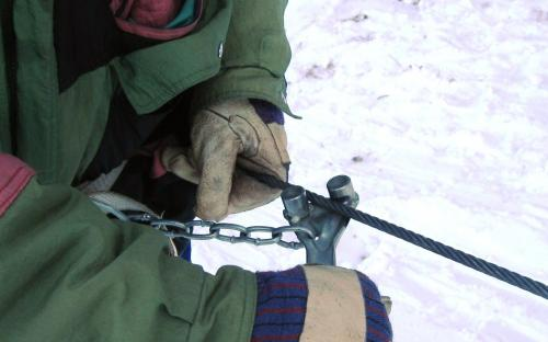 A felvonókulcsot jobb kézzel, felülről megfogjuk és drótkötelet a bütykök közé helyezzük.
